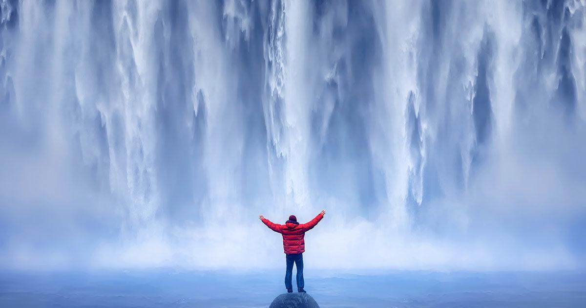 Ihminen seisoo vesiputouksen edessä.