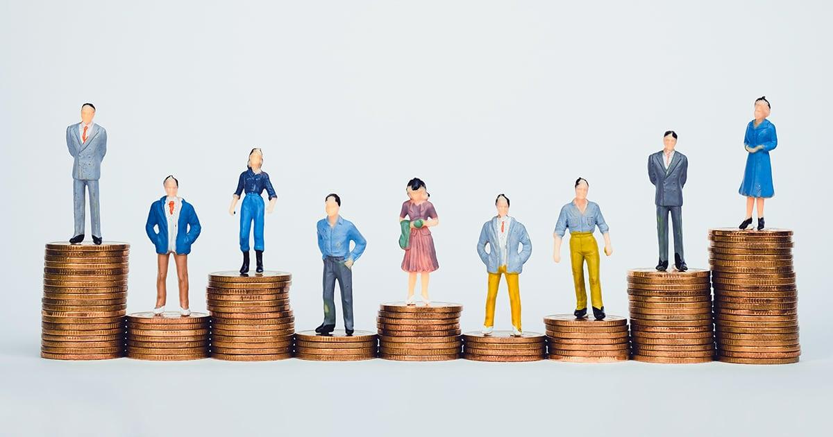 Pieniä hahmoja seisoo rahakasojen päällä